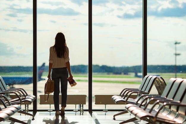 Silhouet van vrouwelijke luchtvaartpassagier in een luchthavenzitkamer die op vluchtvliegtuigen wacht