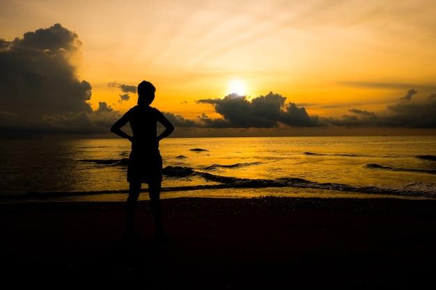 Silhouet van vrouwen die op zonsopgang op het strand kijken, die macht van het leven betekenen.