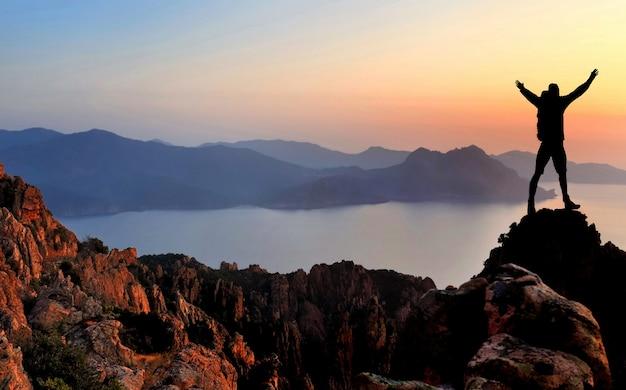 Silhouet van wandelaar die bij de bovenkant van klip bij zonsondergang genieten van
