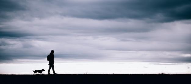 Silhouet van wandelaar en hond