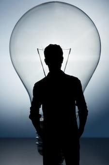 Silhouet van zakenlieden met een gloeilamp achtergrond