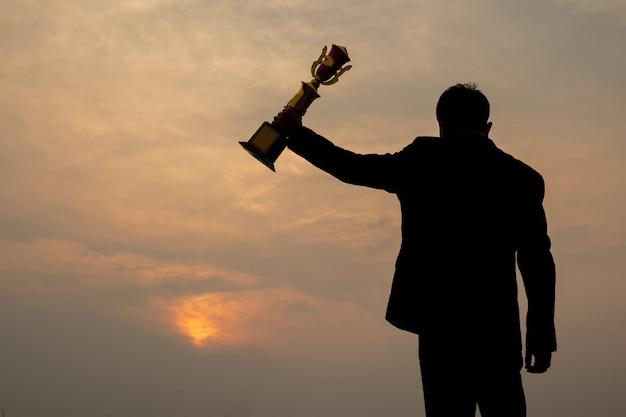 Silhouet van zakenman die zich op berg bevindt die een trofeekop, succes en leiderschapsconcept omhoog houdt.