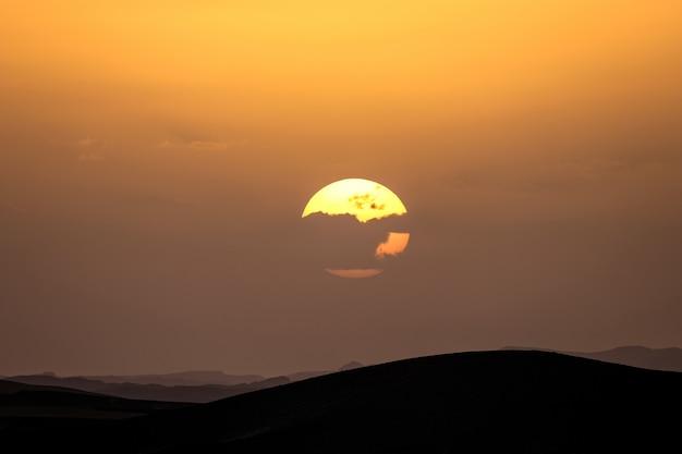 Silhouet van zandduinen met de zon achter een wolk