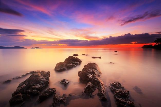 Silhouet van zeegezicht met zonsonderganghemel, lange snelheidsblootstelling, tarn-khu-strand in trat, thailand