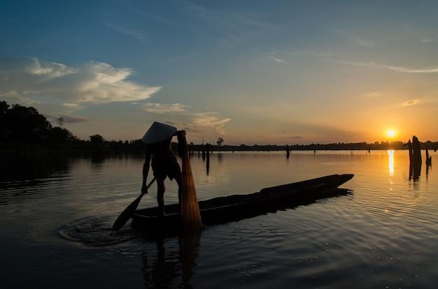 Silhouet visser visnetten op de boot.