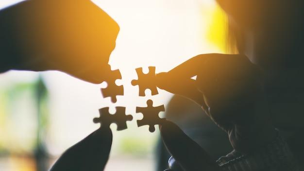Silhouetafbeelding van veel mensen die een stukje witte puzzel vasthouden en in elkaar zetten