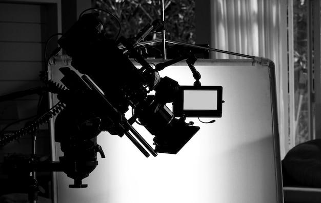 Silhouetafbeeldingen van videocamera in commerciële tv-studioproductie die wordt bediend of gefotografeerd door cameraman en filmploegenteam in set en steun op professionele kraan en statief voor eenvoudig gebruik