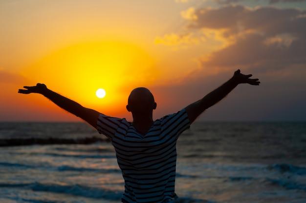 Silhouetbeeld van de mens die zijn handen opheft met straal van licht