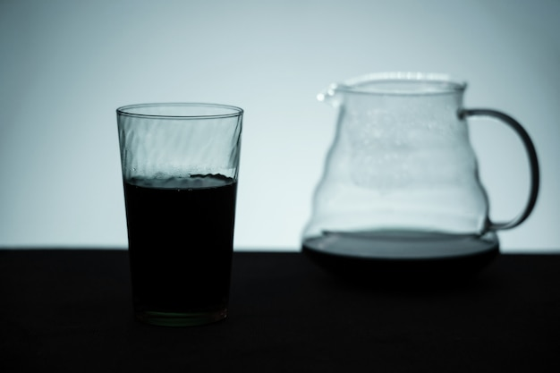 Silhouetbeeld van koffie. een glas met zwarte koffie en een server op tafel