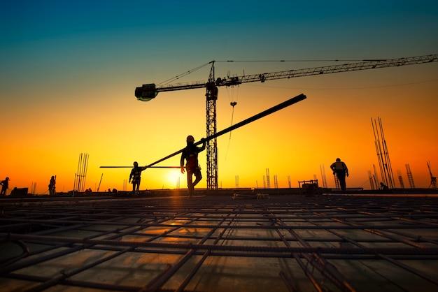 Silhouetbouwvakkers die de bar van de staalversterking vervaardigen bij bouwsi