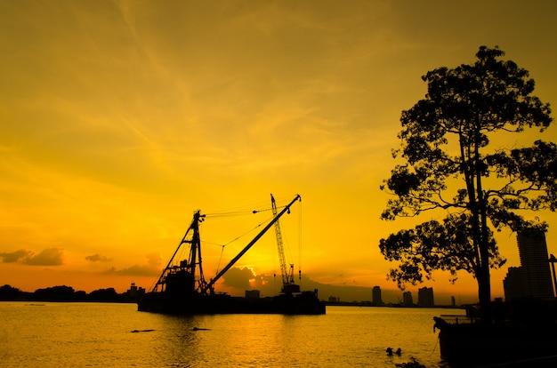 Silhouetbouwwerf die over rivier met bezinning over zonsondergang drijven. bouw concept.
