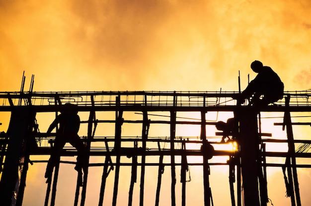 Silhouetbouwwerf met arbeider op zonsondergang.