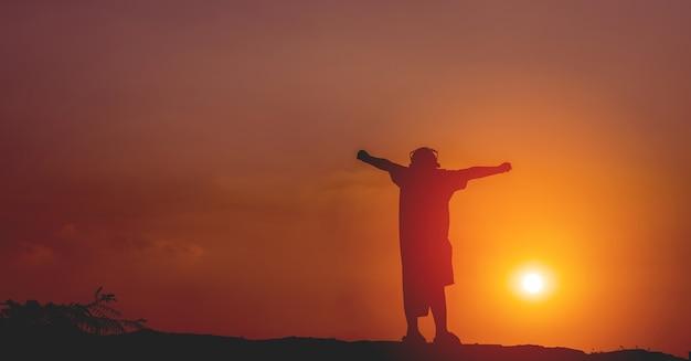 Silhouetconcept van een man die op de berg staat en zonlicht op een warme dag waardoor de lucht donkerder wordt
