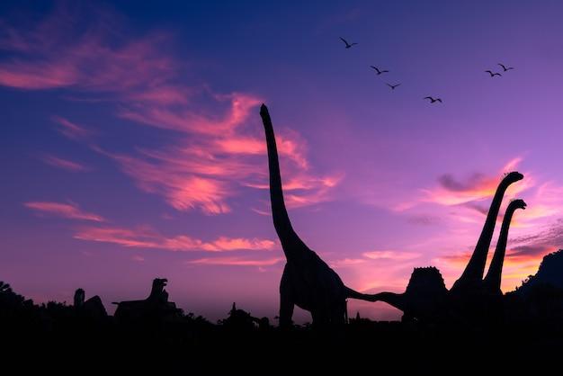 Silhouetdinosaurus in het park en de roze kleuren blauwe hemel