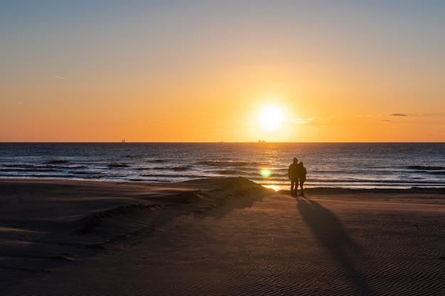 Silhouete van een verliefd paar. mooi zonsonderganglandschap bij de noordzee met oranje hemel en ontzagwekkende zon gouden bezinning over golven in. geweldig uitzicht op de zomer zonsondergang op het strand.