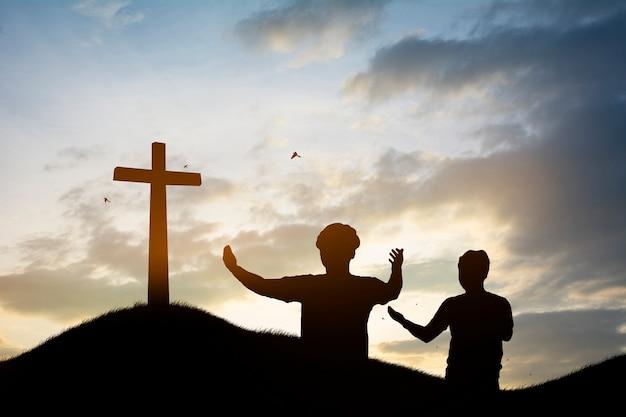Silhouetfamilie die het kruis van jesus-christus op de herfstzonsopgang zoeken