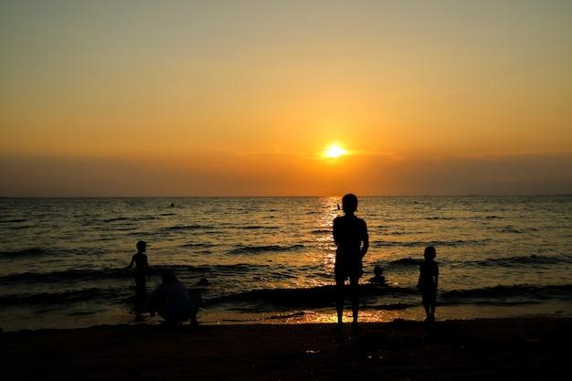 Silhouetfamilie en huisdier bij strand en overzeese zandzonsondergang