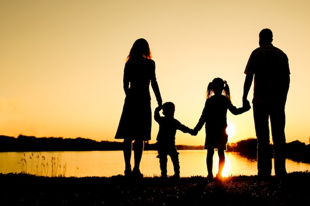 Silhouetfamilie, inclusief zijn vader, moeder en twee kinderen in handen van