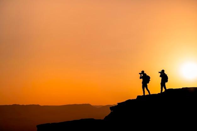 Silhouetfotografen die een zonsondergang in de bergen schieten. fotograaf concept