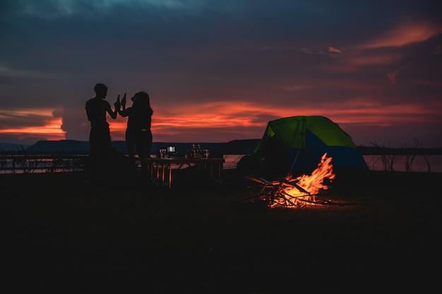 Silhouetgroep aziatische vriendentoerist die en gitaar samen met geluk in de zomer drinken spelen terwijl het hebben van het kamperen dichtbij meer