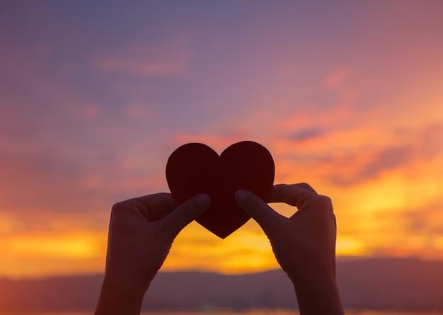 Silhouethand die mooi hart houden tijdens zonsondergangachtergrond