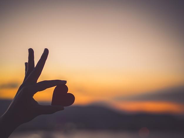Silhouethand die mooi hart houden tijdens zonsondergangachtergrond.
