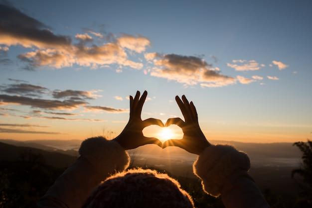 Silhouethanden die een hartvorm met zonsopgang vormen