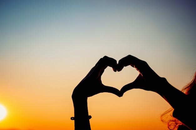 Silhouethanden die hartvorm met zonsondergang vormen