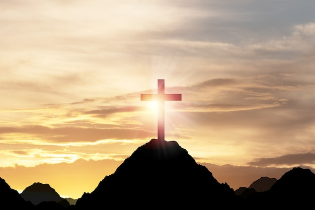Silhouetkruis of kruisiging van jesus christian bovenop berg met zonlicht en wolkenhemel. christendom religie concept.