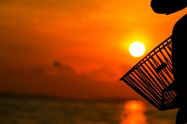 Silhouetmand op motor en zonsondergang op zee