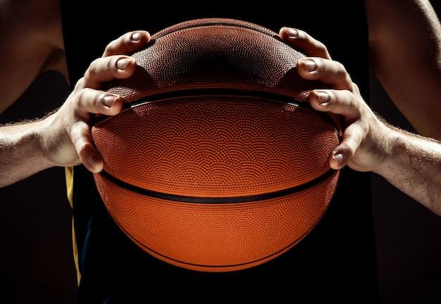Silhouetmening van een bal van de de holdingsmand van de basketbalspeler op zwarte muur