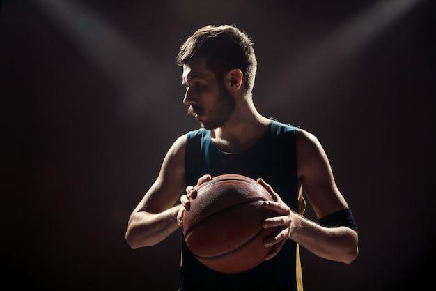 Silhouetmening van een bal van de de holdingsmand van de basketbalspeler op zwarte