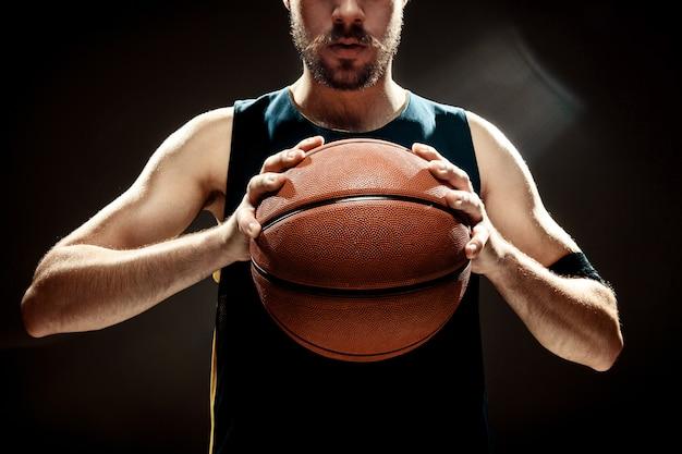 Silhouetmening van een basketbalbal van de de holdingsmand van de basketbalspeler op zwarte muur