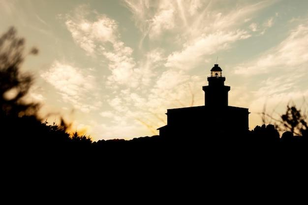 Silhouetmening van vuurtoren in capo testa bij zonsondergang - sardinige.