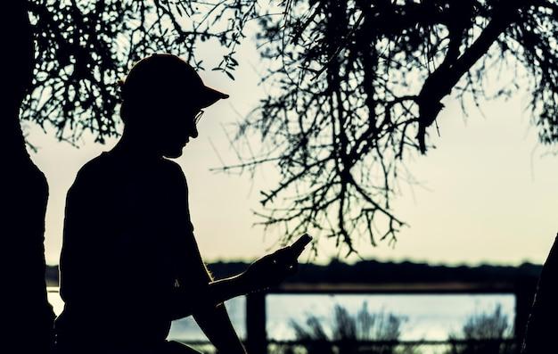 Silhouetmens die smartphone met dode boom gebruiken