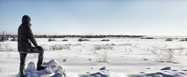 Silhouetmensen staan op een zonnige dag in een winterveld