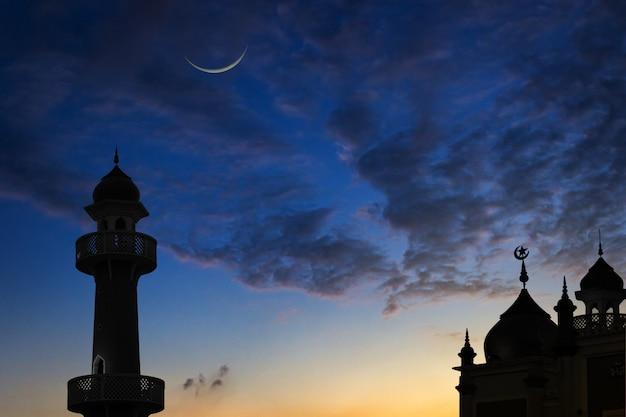 Silhouetmoskeeën en een toenemende maan bij zonsondergang