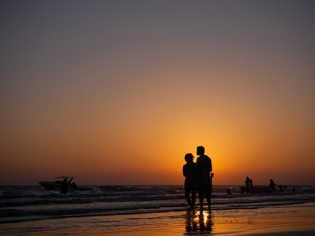 Silhouetpaar die in liefde op strand met de oranje achtergrond van de avondhemel lopen.