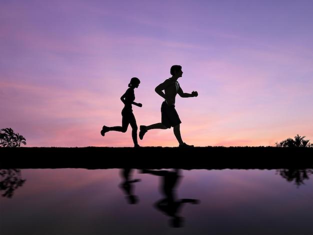 Silhouetpaar joggen met twilight sky background
