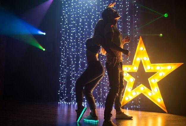 Silhouetpaar van liefdevolle jonge man en vrouw die dansen en plezier hebben in een nachtclub op een feestje
