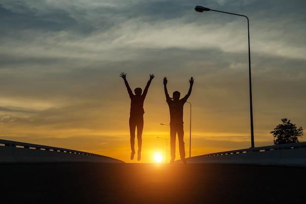 Silhouetparen die bij zonsondergang springen