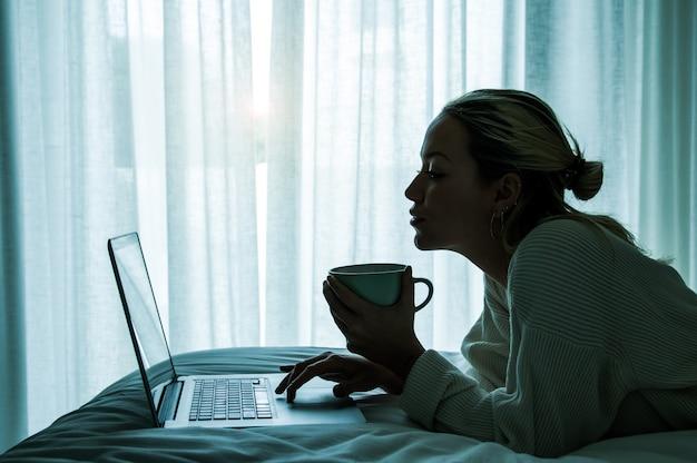 Silhouetportret van een jonge vrouw die op het bed liggen die thuis koffie drinken terwijl het gebruiken van pc-laptop. slim werkconcept