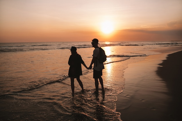 Silhouetportret van jong romantisch paar dat op het strand loopt. meisje en haar vriend poseren bij gouden kleurrijke zonsondergang