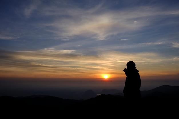 Silhouetstijl. knappe jongeman stond koffie te nippen. het bewonderen van de schoonheid van aard tijdens zonsopgang gouden uur. mistig uitzicht op de bergen en mooi van bovenaf.