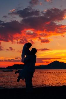 Silhouetten bij zonsondergang op het strand