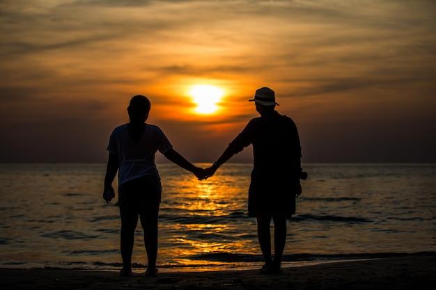 Silhouetten die zich door de zee en de oranje hemel.