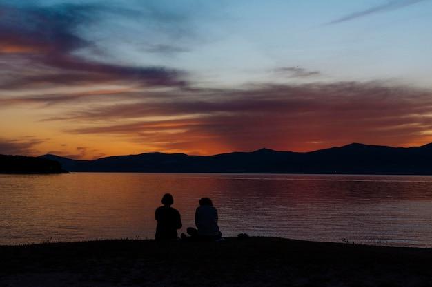 Silhouetten op mensen op het strand bij zonsondergang