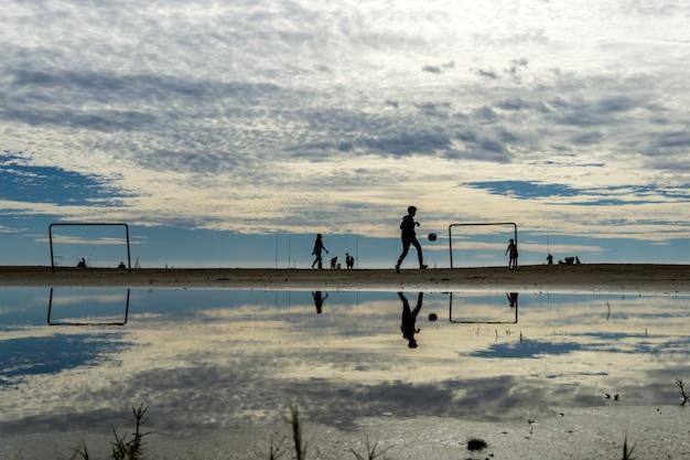 Silhouetten spelen op het strand