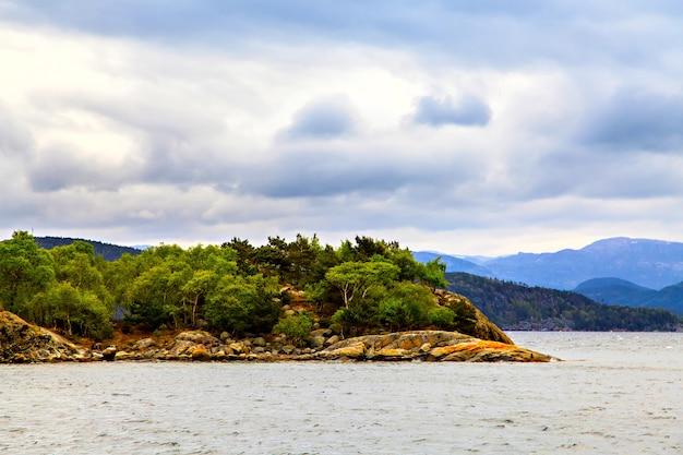 Silhouetten van bergen en bomen die op de heuvel aan zee groeien growing