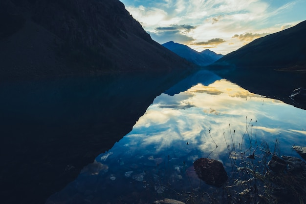 Silhouetten van bergen en weerspiegeling van zonsondergang bewolkte hemel in glad meerwater